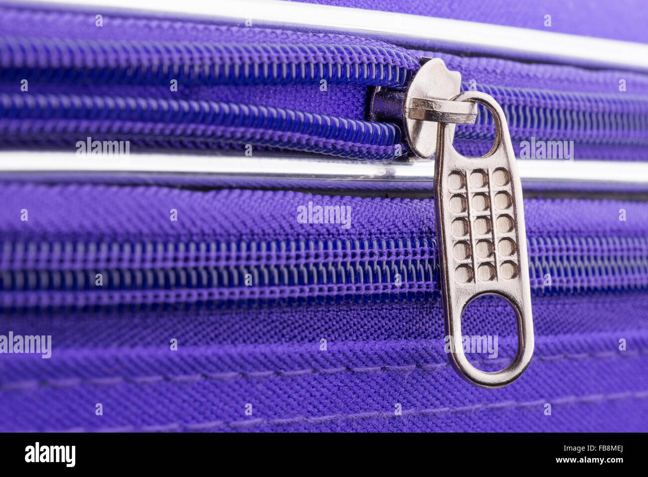 Macro of a zipper showing the pull tab and the chain on a violet suitcase ready for a safe holiday travel - Stock Image