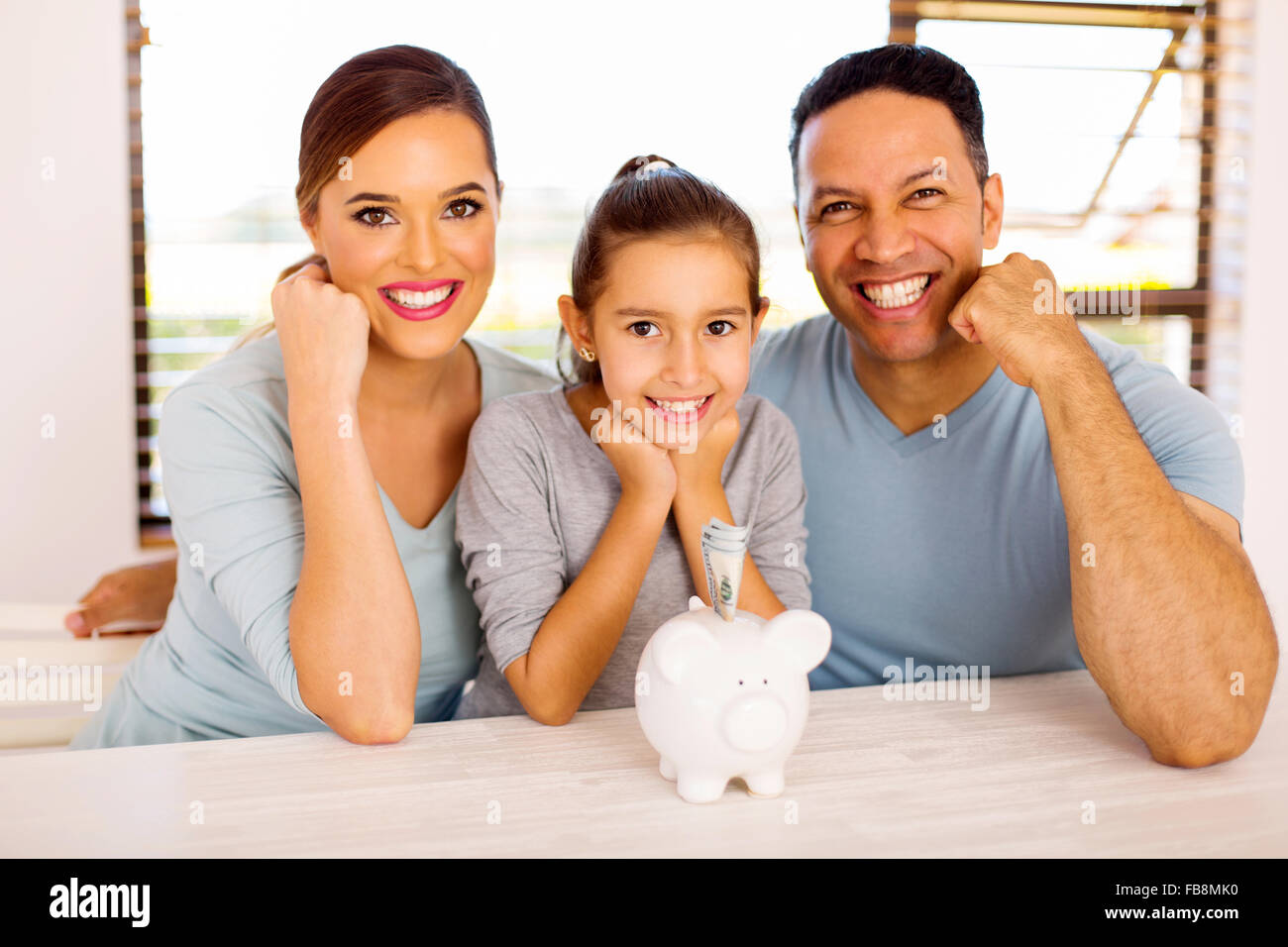 cheerful family of three with piggybank at home - Stock Image