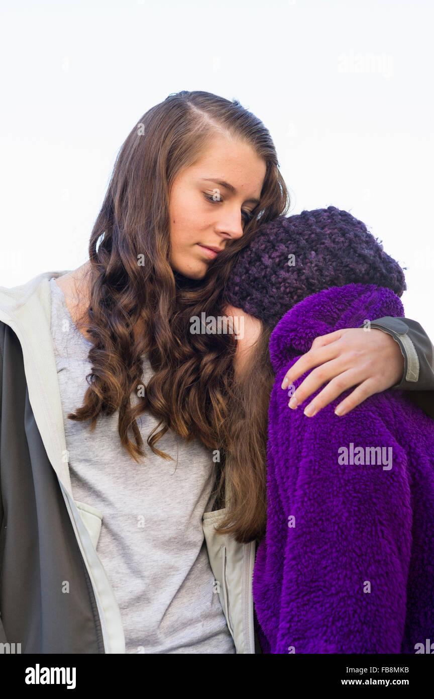 Sweden, Sodermanland, Stigtomta, Teenage girl (14-15) embracing her younger friend (10-11) - Stock Image