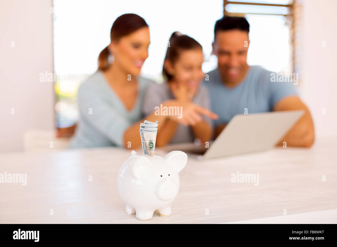 family doing home financial planning with piggybank in front - Stock Image
