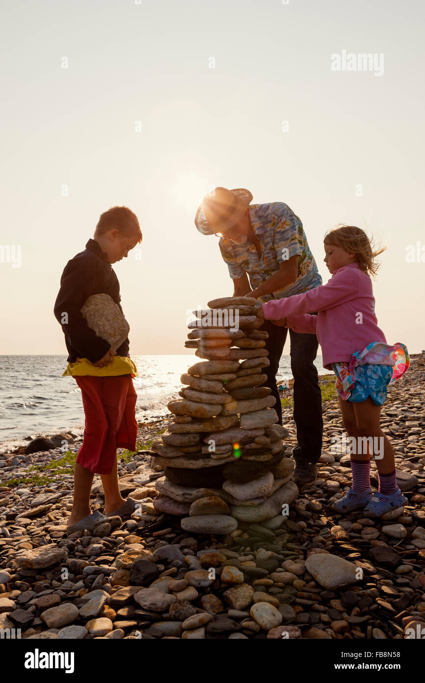 Sweden, Oland, Gronhogen, Grandfather and grandchildren (6-7), (10-11) making stone heaps - Stock Image