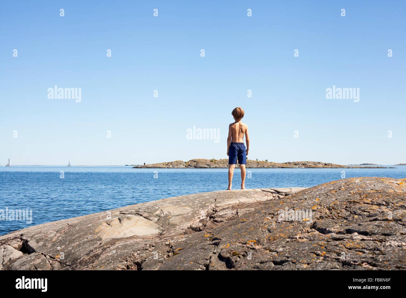 Sweden, Uppland, Runmaro, Barrskar, Rear view of boy (6-7) looking at sea - Stock Image