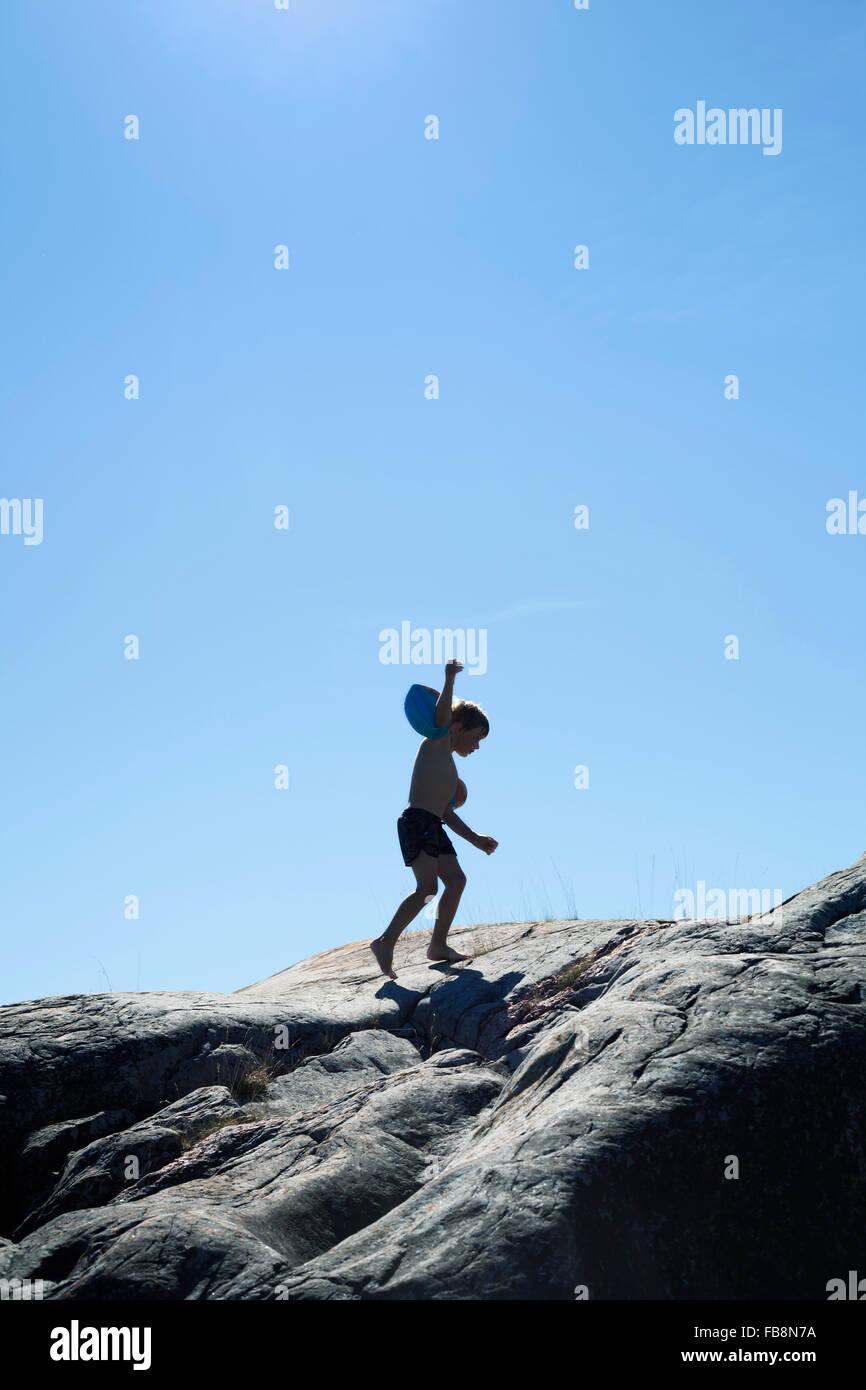 Sweden, Uppland, Runmaro, Barrskar, Boy (4-5) with water wings walking on seaside - Stock Image