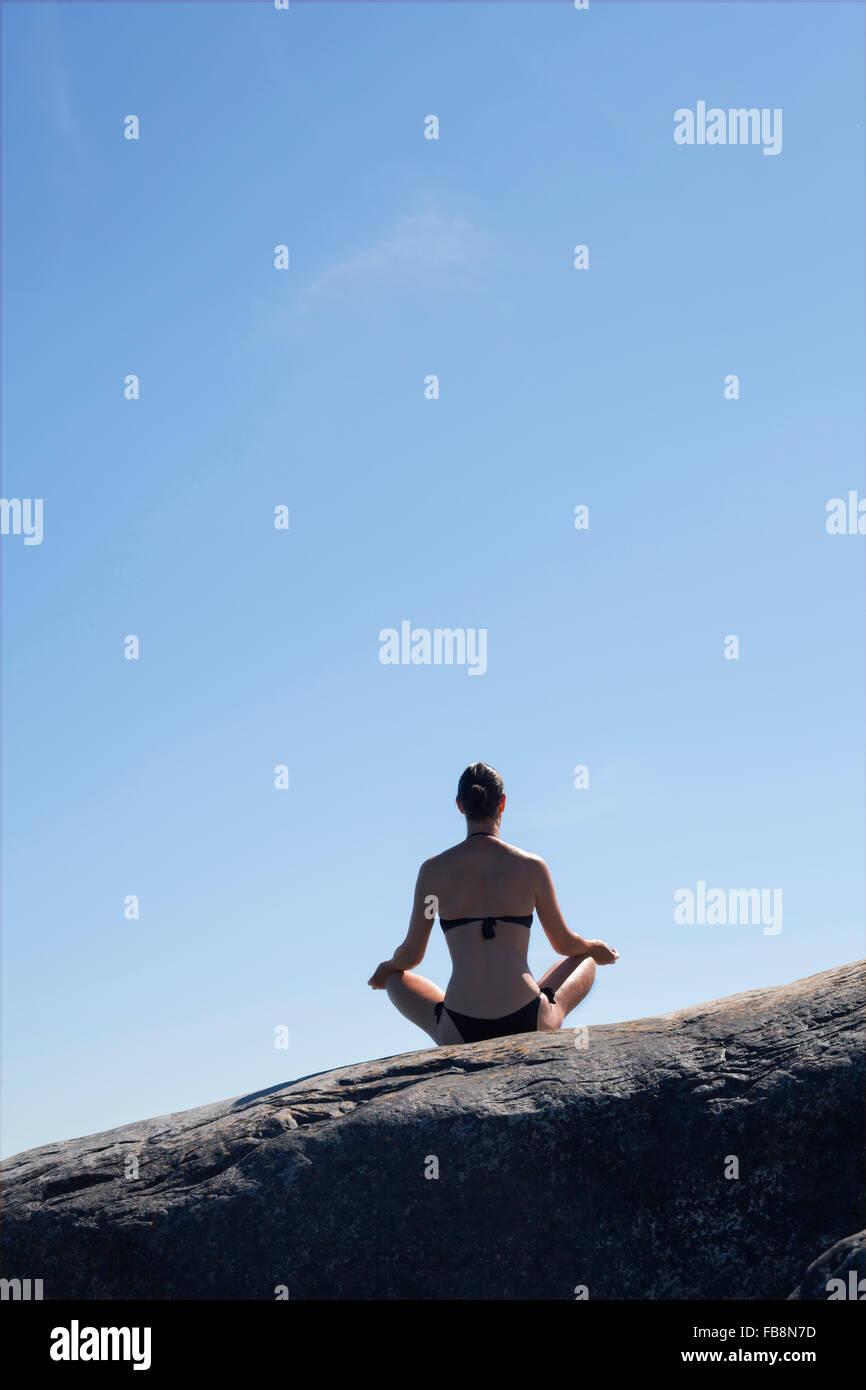 Sweden, Uppland, Runmaro, Barrskar, Rear view of woman practicing yoga on rock - Stock Image