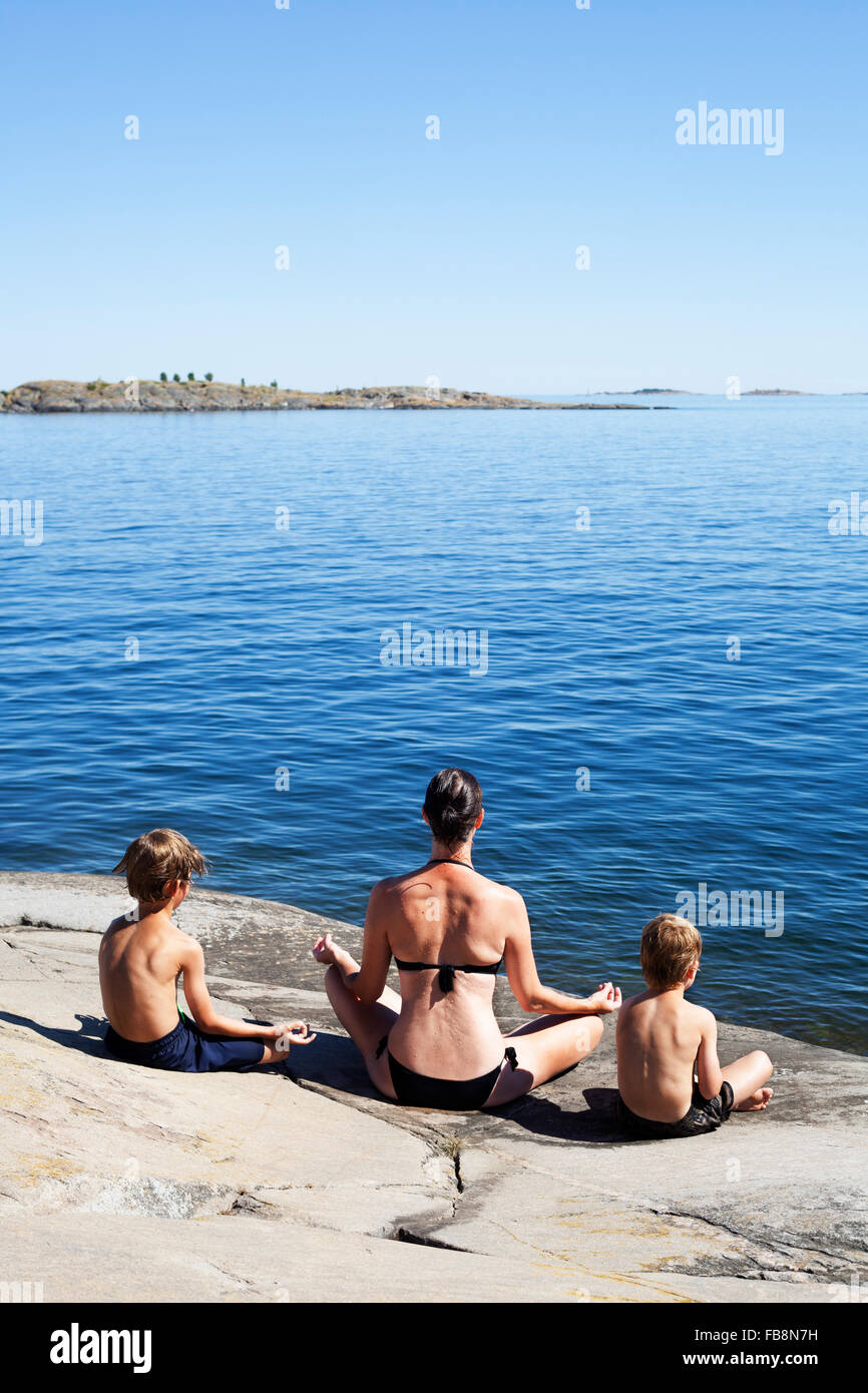 Sweden, Uppland, Runmaro, Barrskar, Rear view of mother and sons practicing yoga on seaside - Stock Image