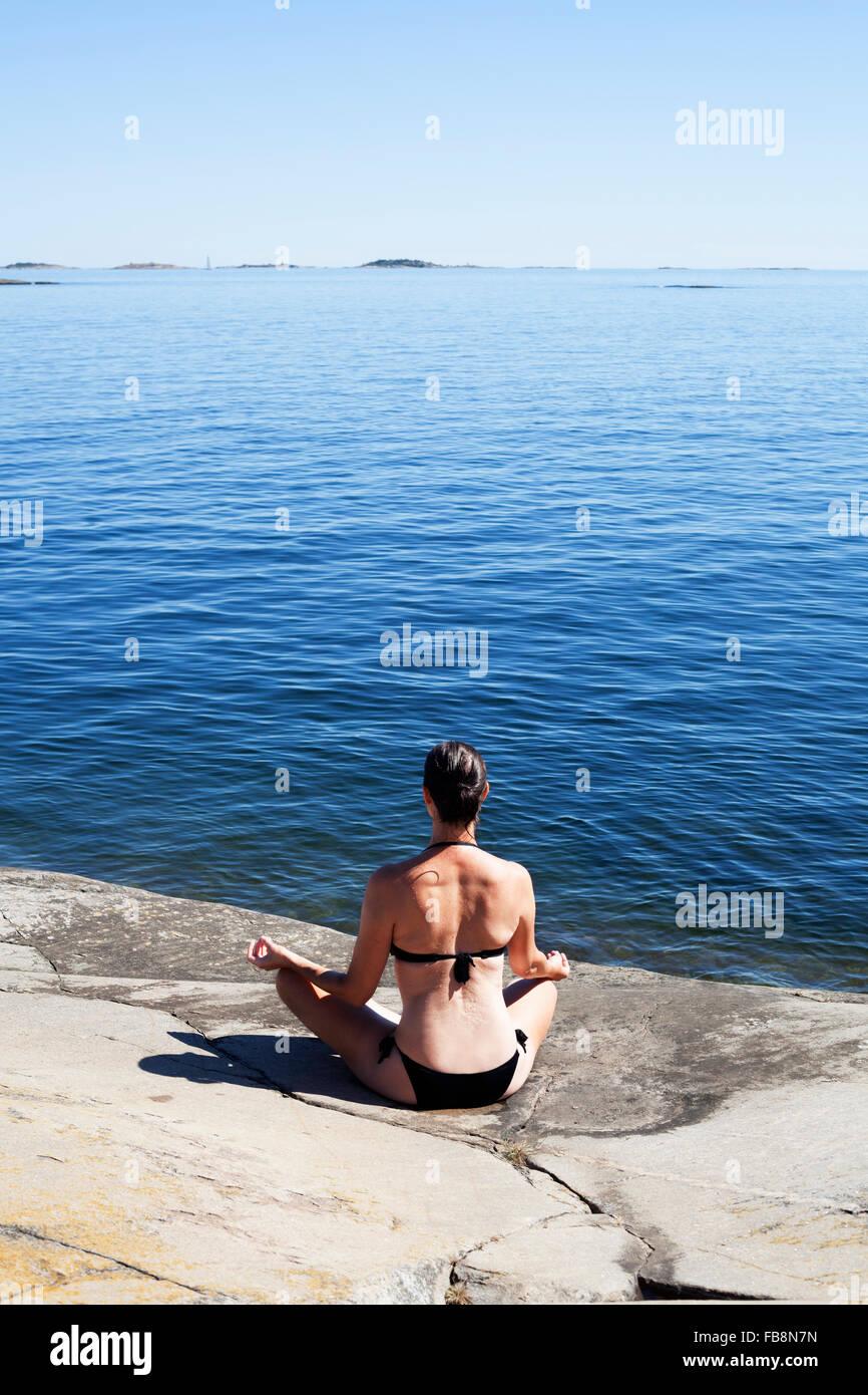 Sweden, Uppland, Runmaro, Barrskar, Rear view of woman practicing yoga on seaside - Stock Image