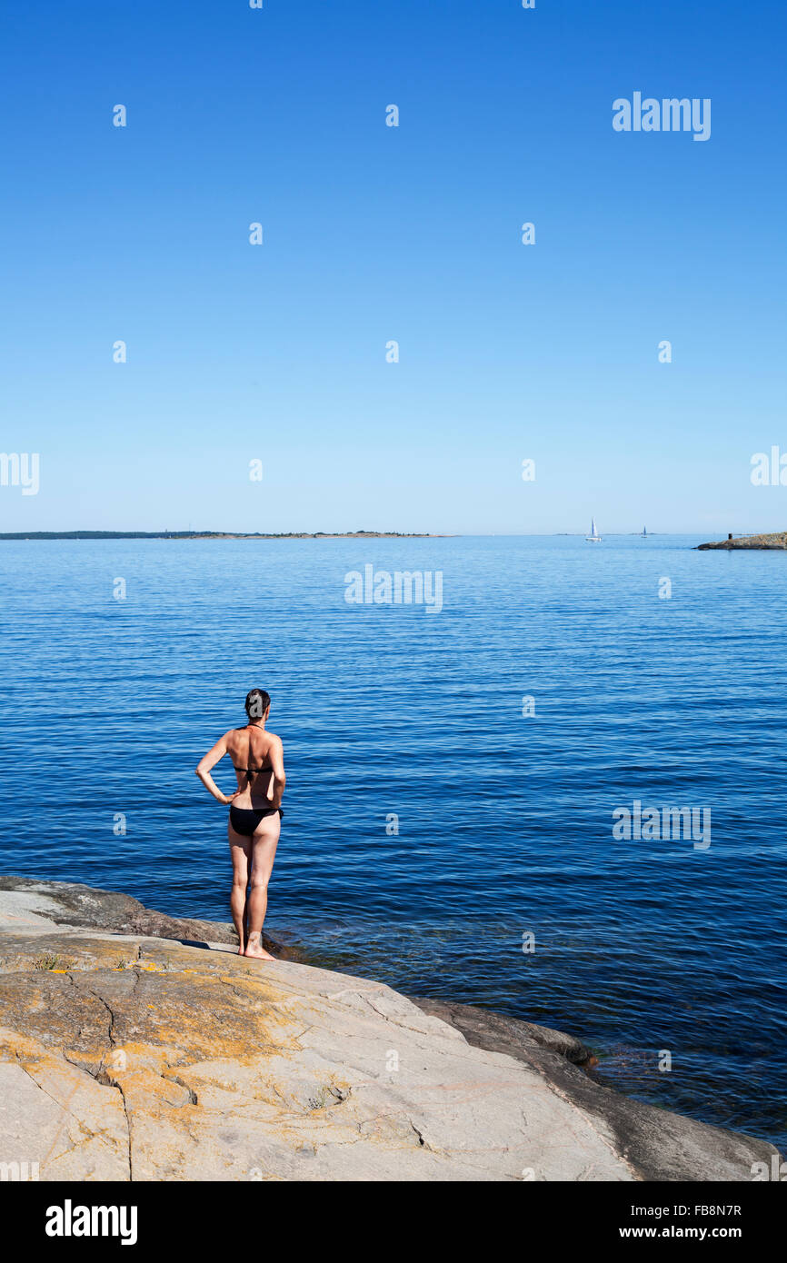 Sweden, Uppland, Runmaro, Barrskar, Woman standing on seaside and looking at view - Stock Image