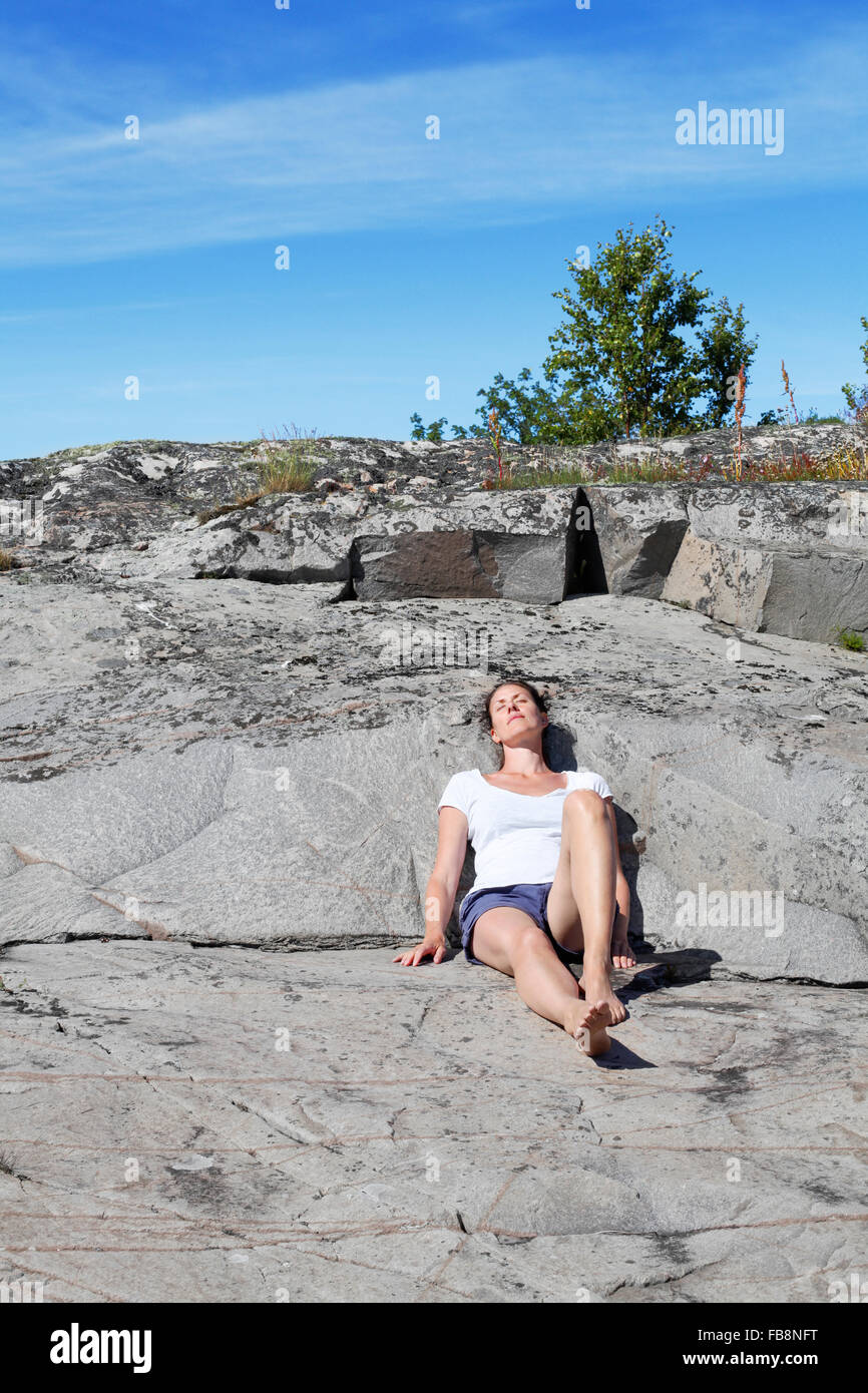 Sweden, Uppland, Runmaro, Barrskar, Woman relaxing on rock - Stock Image