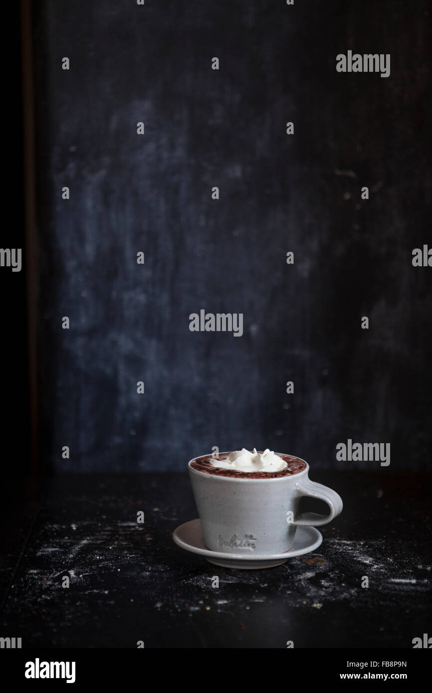 Cup of hot chocolate in dark room - Stock Image
