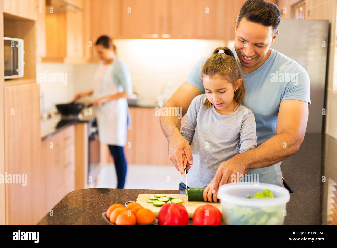 father teaching little daughter cutting vegetables while mother cooking on background - Stock Image