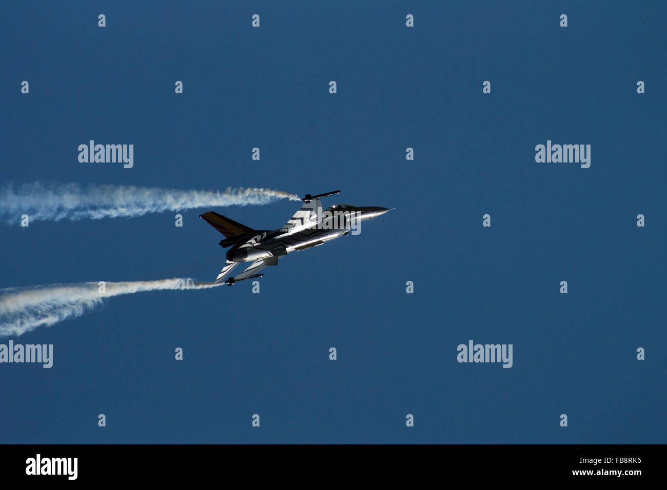 Fighter jet aeroplane with missiles against dark blue sky with white smoke at air show. International Air Tattoo Stock Photo