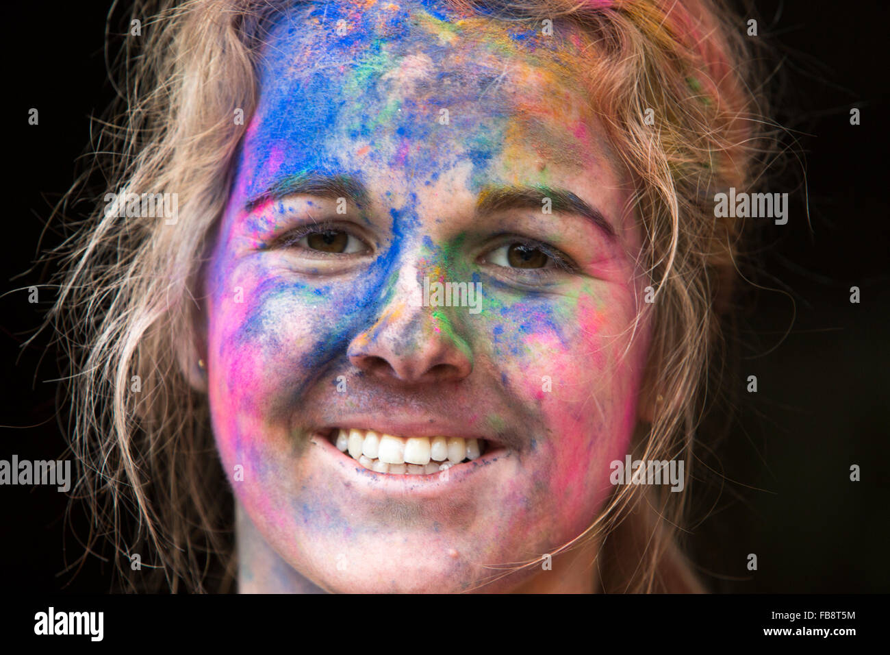 Pretty teenage girl with her face splattered with colourful paint after participating in the Colour Run - Stock Image