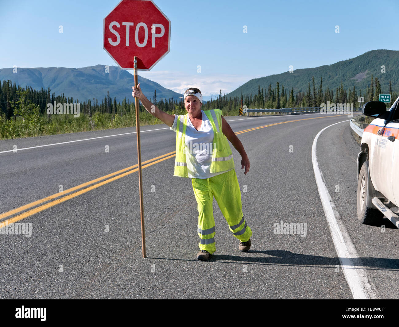 Traffic control, female wearing safety colors, displaying 'stop' sign, Alcan Highway. - Stock Image