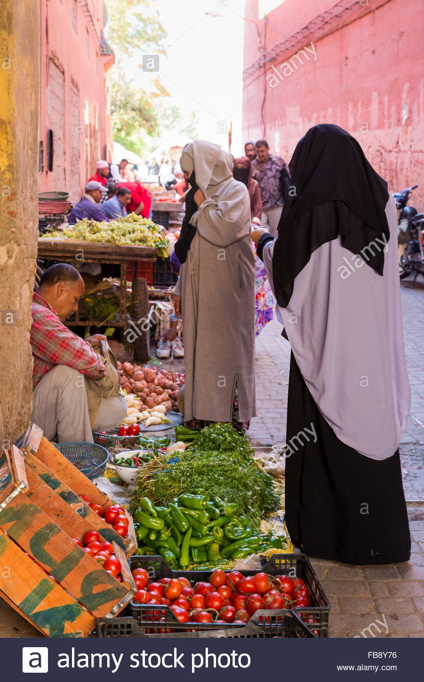Women wearing traditional djellaba and headscarf (niqab) shopping at the fruit and vegetable market in the souks - Stock Image