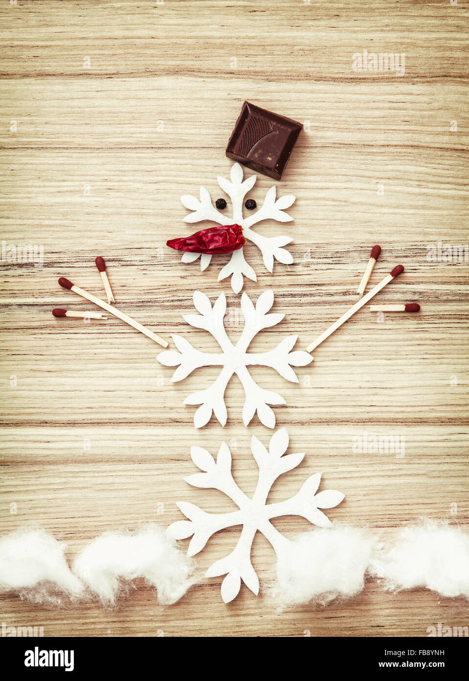 beautiful snowman made of snow flakes matches chocolate and chili peppers on the wooden background symbol of winter