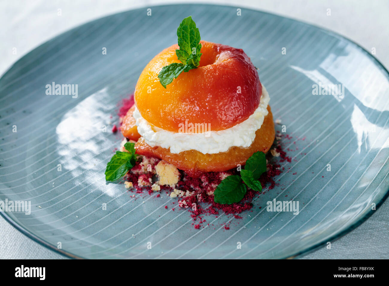 Roast peach with cream, crumbled biscuit and raspberry powder - Stock Image
