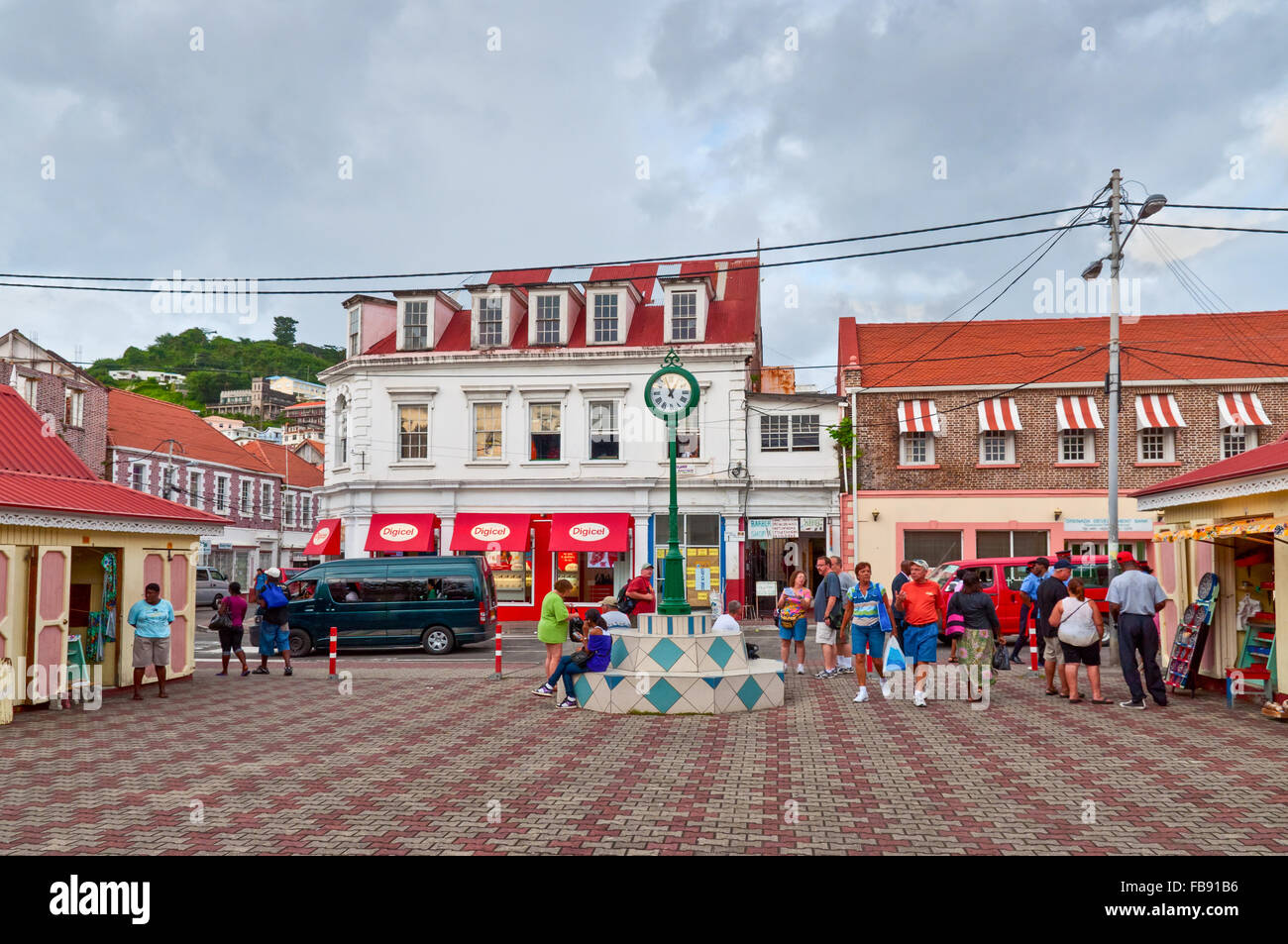 Scene of daily life in the capital of Grenada, with people walking on the sidewalks and traffic in the streets. - Stock Image