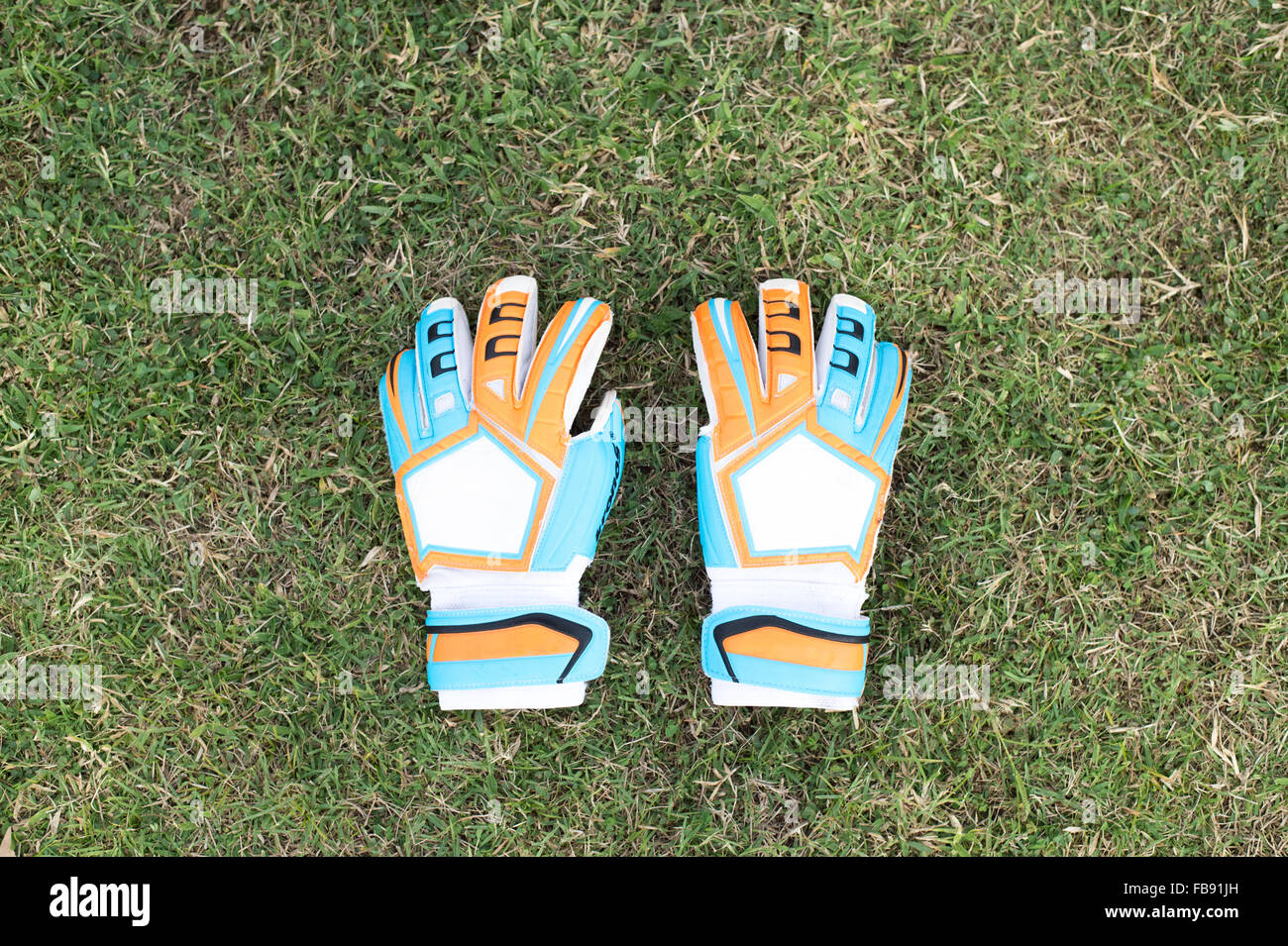 Goalkeeper Gloves Laying on the grass in the stadium - Stock Image