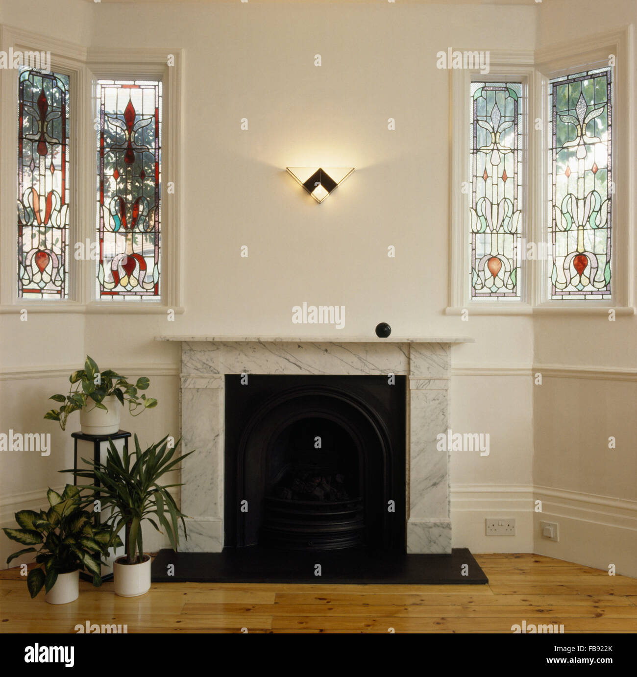 Stained glass windows either side of marble fireplace - Stock Image