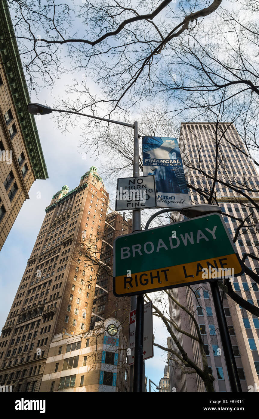 Looking up at traffic signs in Financial District with Broadway directions and no horn honking sign with towers - Stock Image