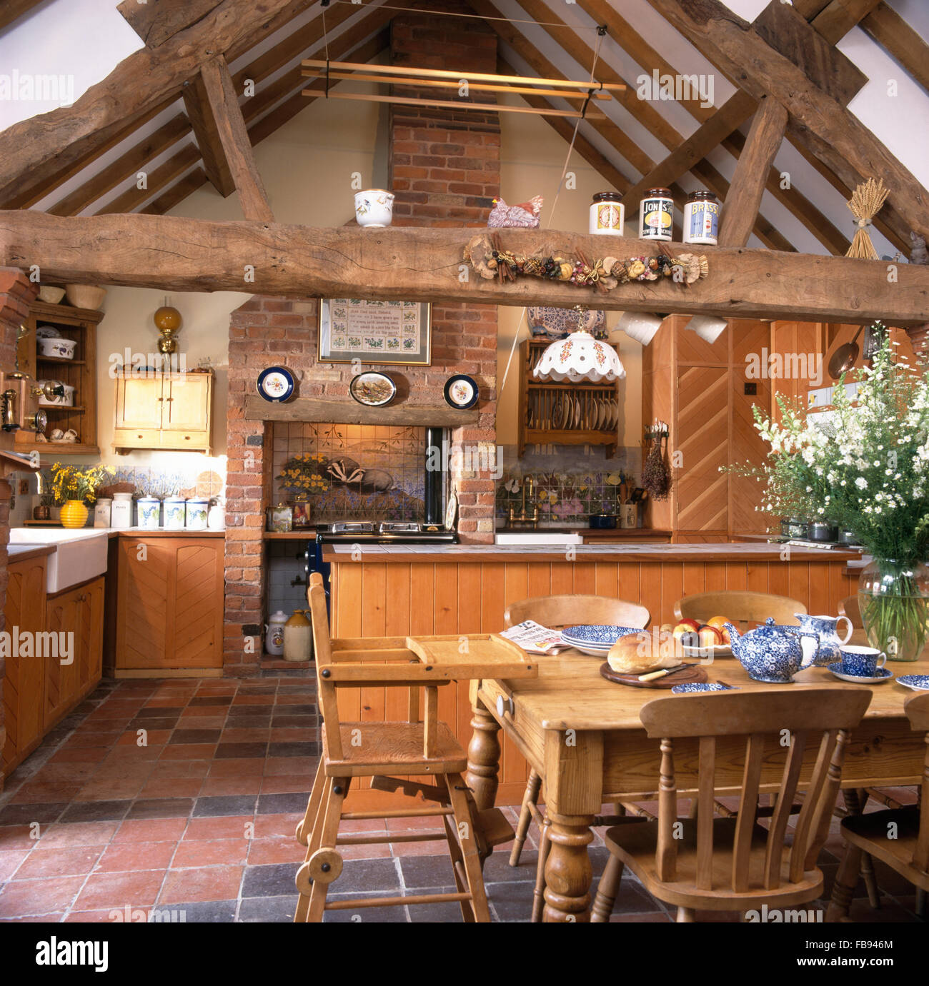 Wooden Chairs And Childu0027s High Chair At Pine Table In Barn Conversion  Kitchen With Rustic Wooden Beams