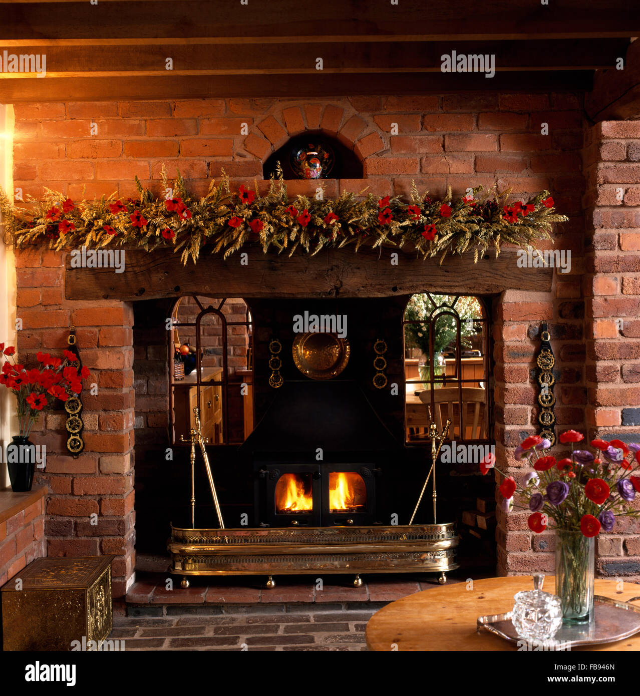 Arched interior windows either side of wood burning stove with a brass fender in fireplace with dried flower garland - Stock Image