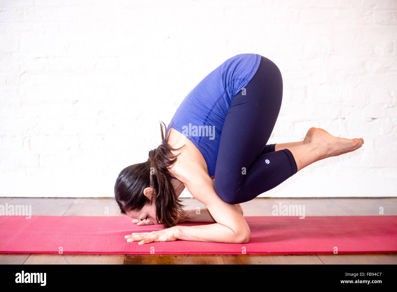 woman doing yoga turtle pose balancing knees on the back of arms - Stock Image