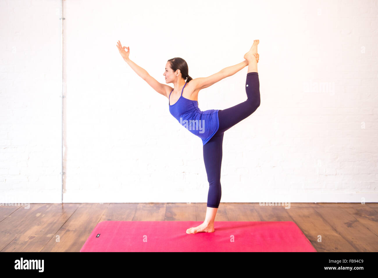 woman doing yoga pose on mat - Stock Image