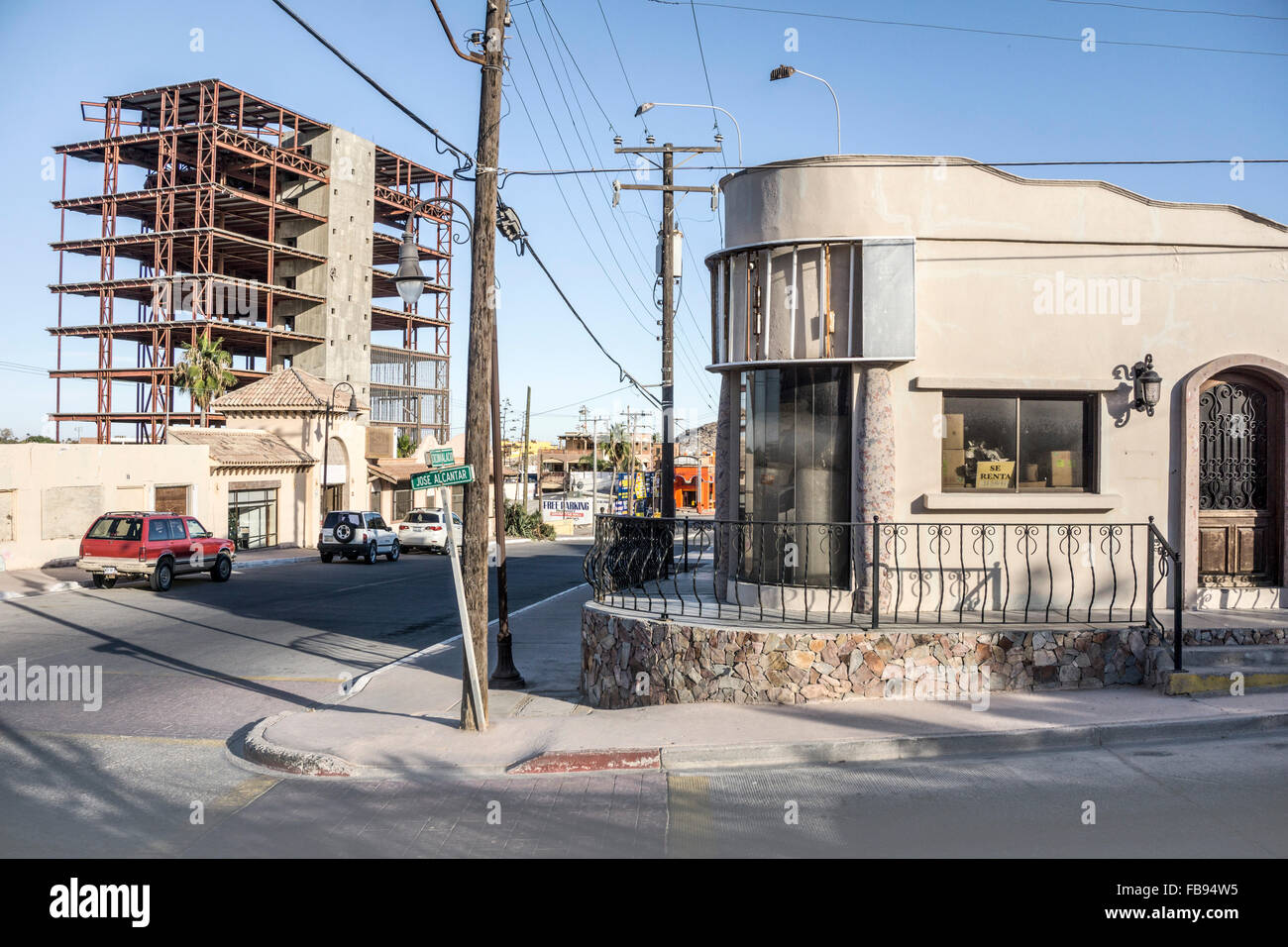 corner building with Art Deco curves crudely altered & now unoccupied & steel frame of abandoned construction - Stock Image