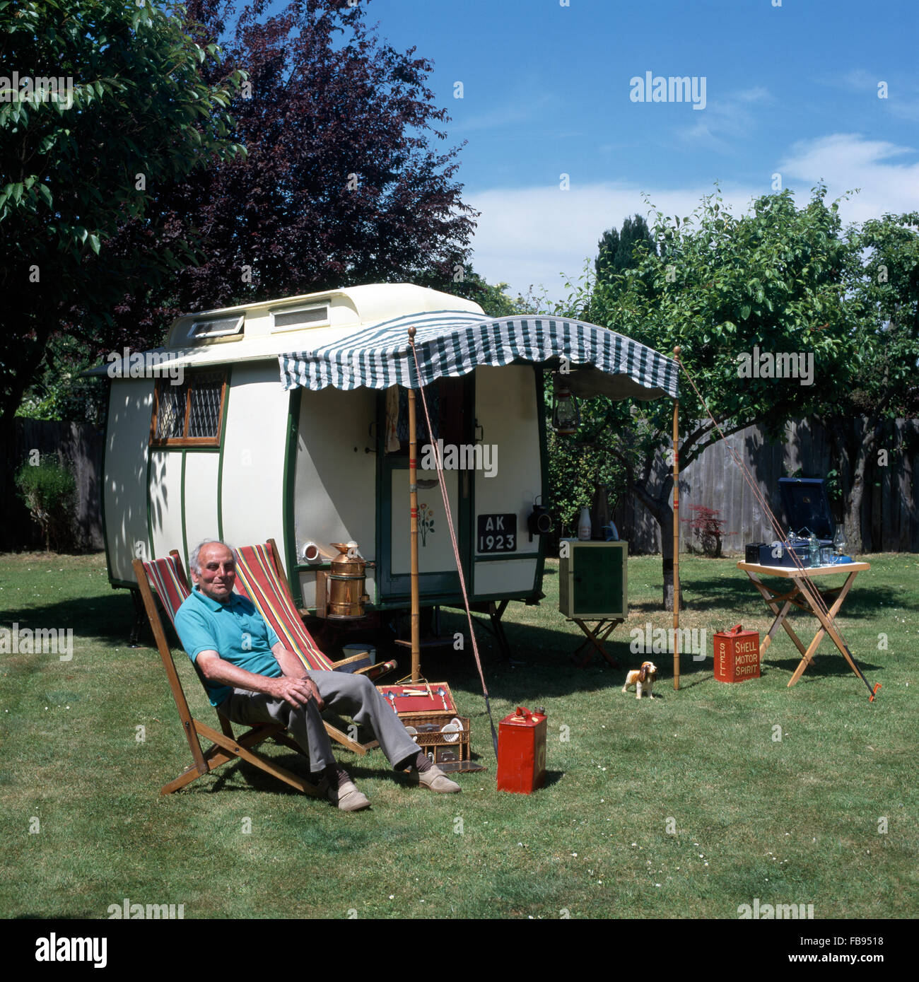Portrait of man relaxing in old deckchair beside fifties caravan with striped awning         FOR EDITORIAL USE ONLY - Stock Image