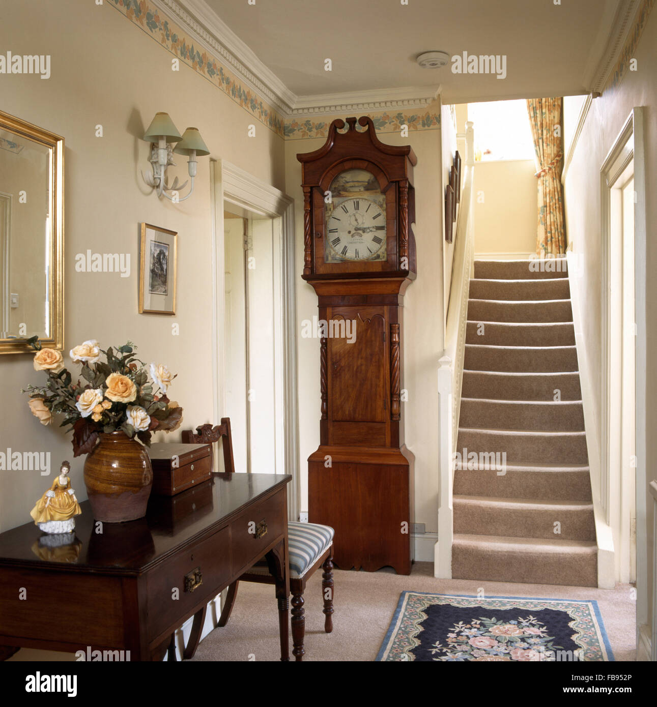 Antique long case clock in country hall with an antique console table - Stock Image