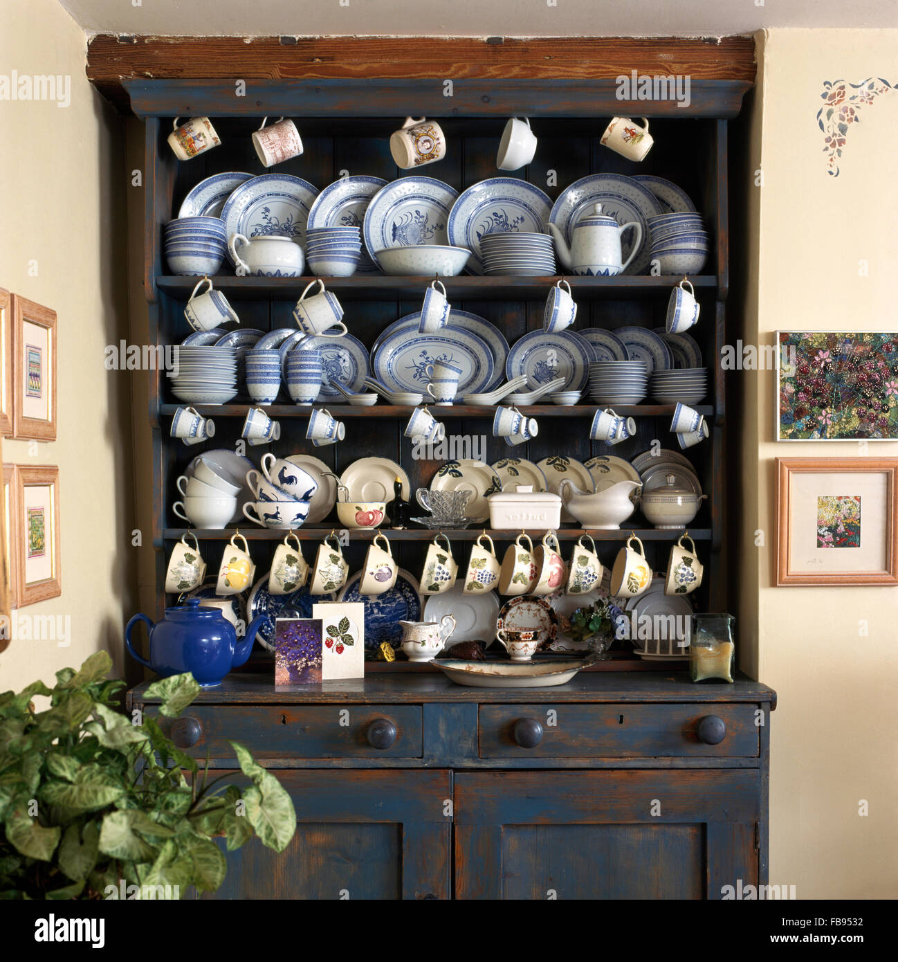 Collection of china on a painted dresser in a country dining room - Stock Image
