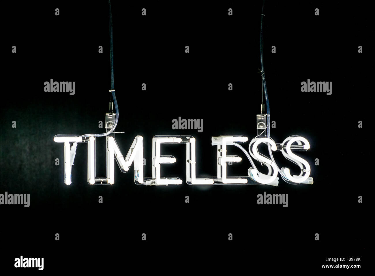 Illuminated white Timeless neon sign on a dark black background with copy space above - Stock Image