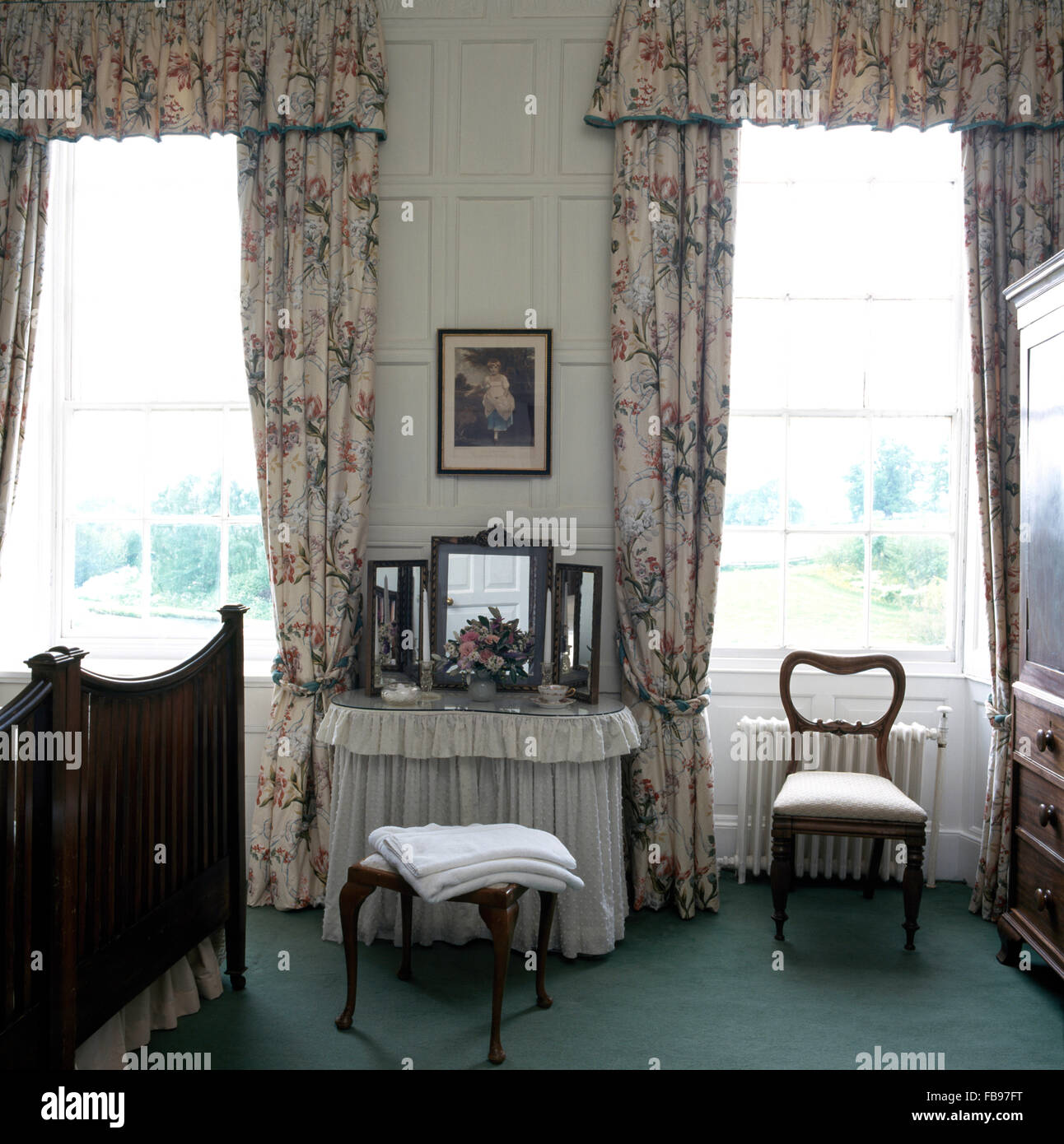 Kidney Shaped Dressing Table With White Drapes Between Tall Windows Floral Curtains In Large Country Bedroom