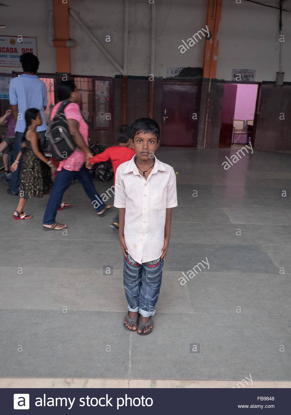A boy waiting for a train at Alleppey train station - Stock Image