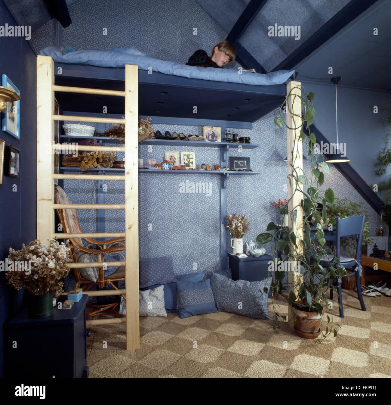 Teenage Boy Lying On Platform Bed In A Blue Seventies Attic Bedroom Stock Photo Alamy