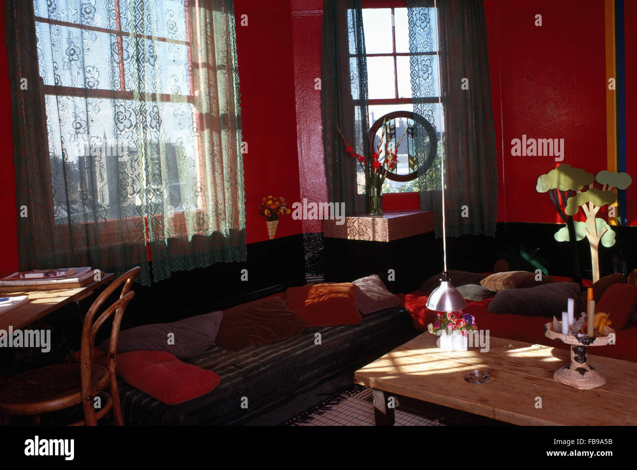 Lace Curtains On Window Above Cushions On Divan Sofa In Red Sixties  Apartment Living Room