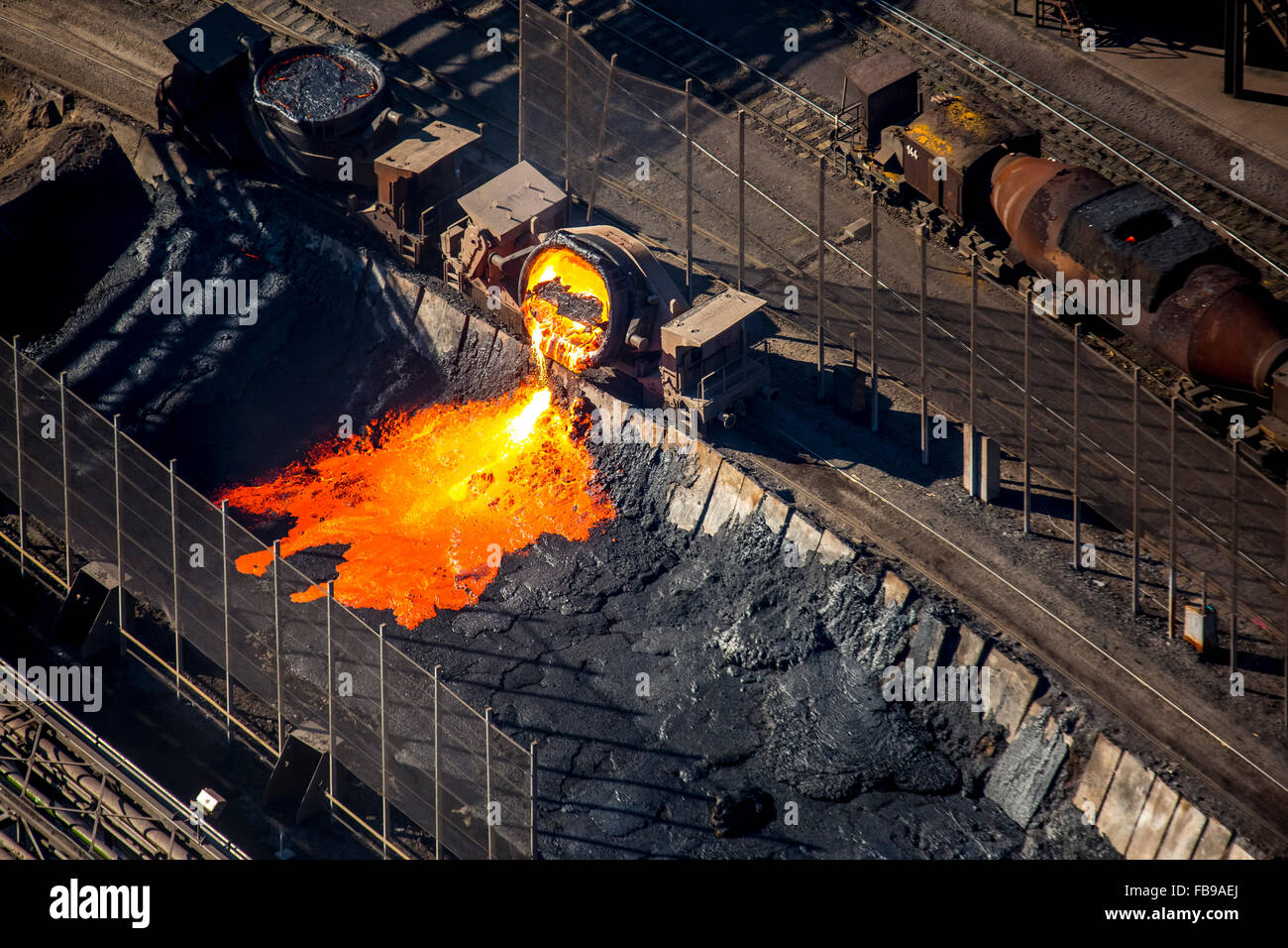 Aerial view, hot slag from the iron production is tipped from a torpedo ladle car into a pit, slag carriage in steel - Stock Image