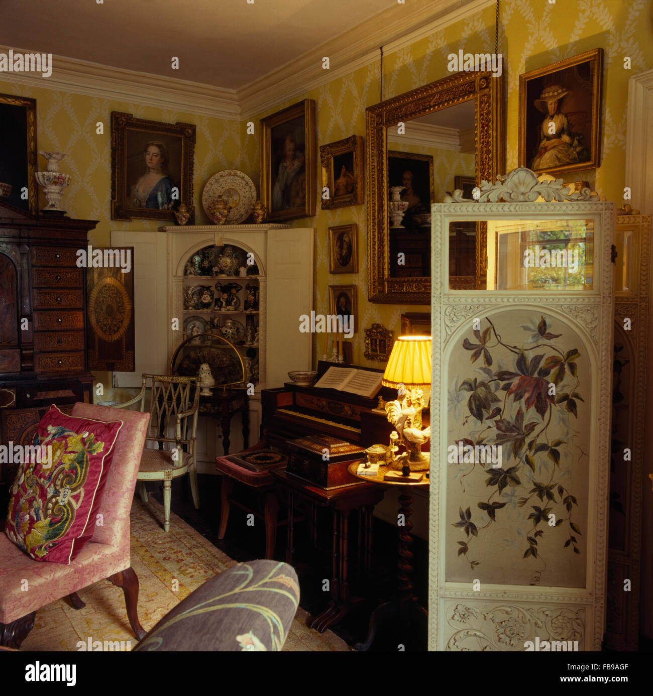 Painted antique folding screen in drawing room in Jacobean rectory with antique furniture and a lighted lamp Stock Photo