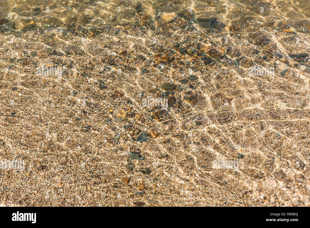 Transparent clear water and pebbles with sunlight reflection - Stock Image