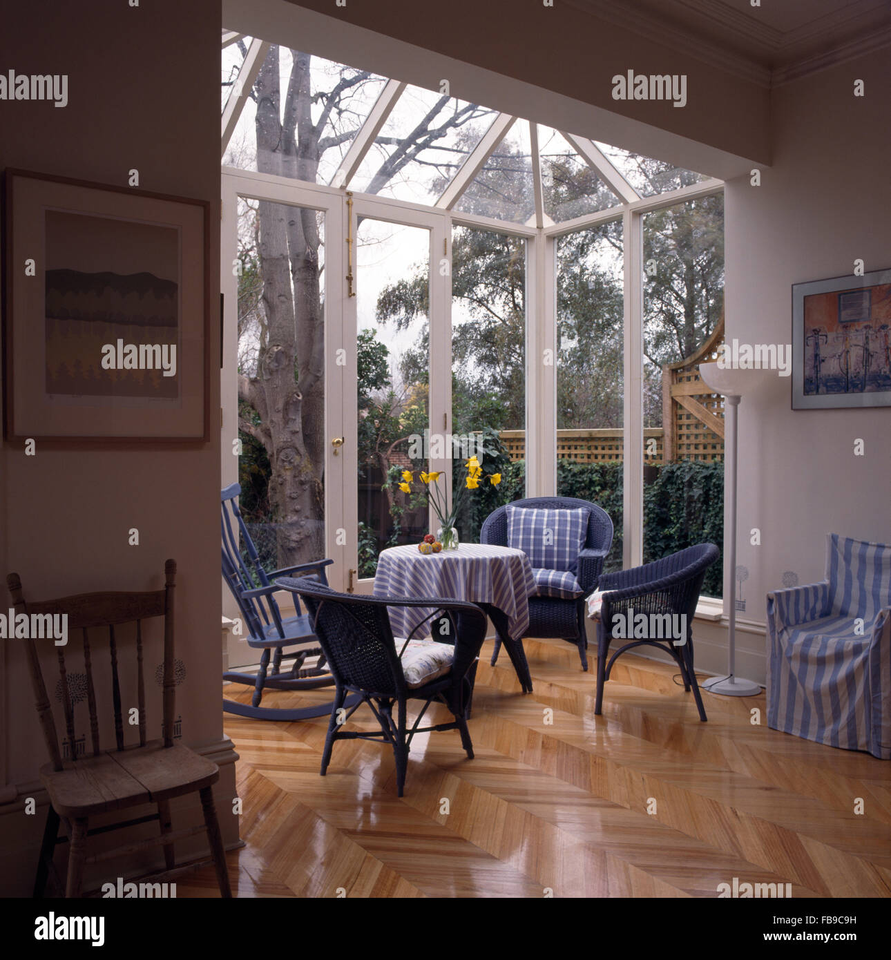 Parquet flooring and wicker chairs in an open plan, glass extension dining room - Stock Image
