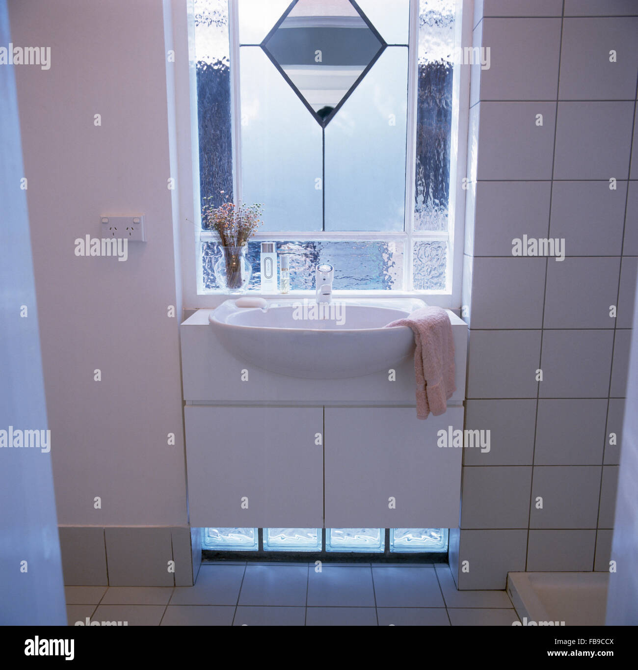 Engraved and opaque glass window above fitted basin in nineties tiled bathroom - Stock Image