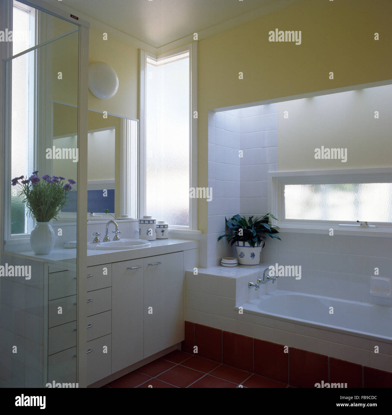 White vanity unit and tiling in pale yellow nineties bathroom with a narrow window above a low fitted bath - Stock Image