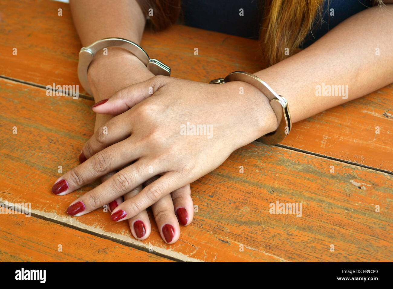 Female prisoner being investigated with hands cuffed on a table - Stock Image