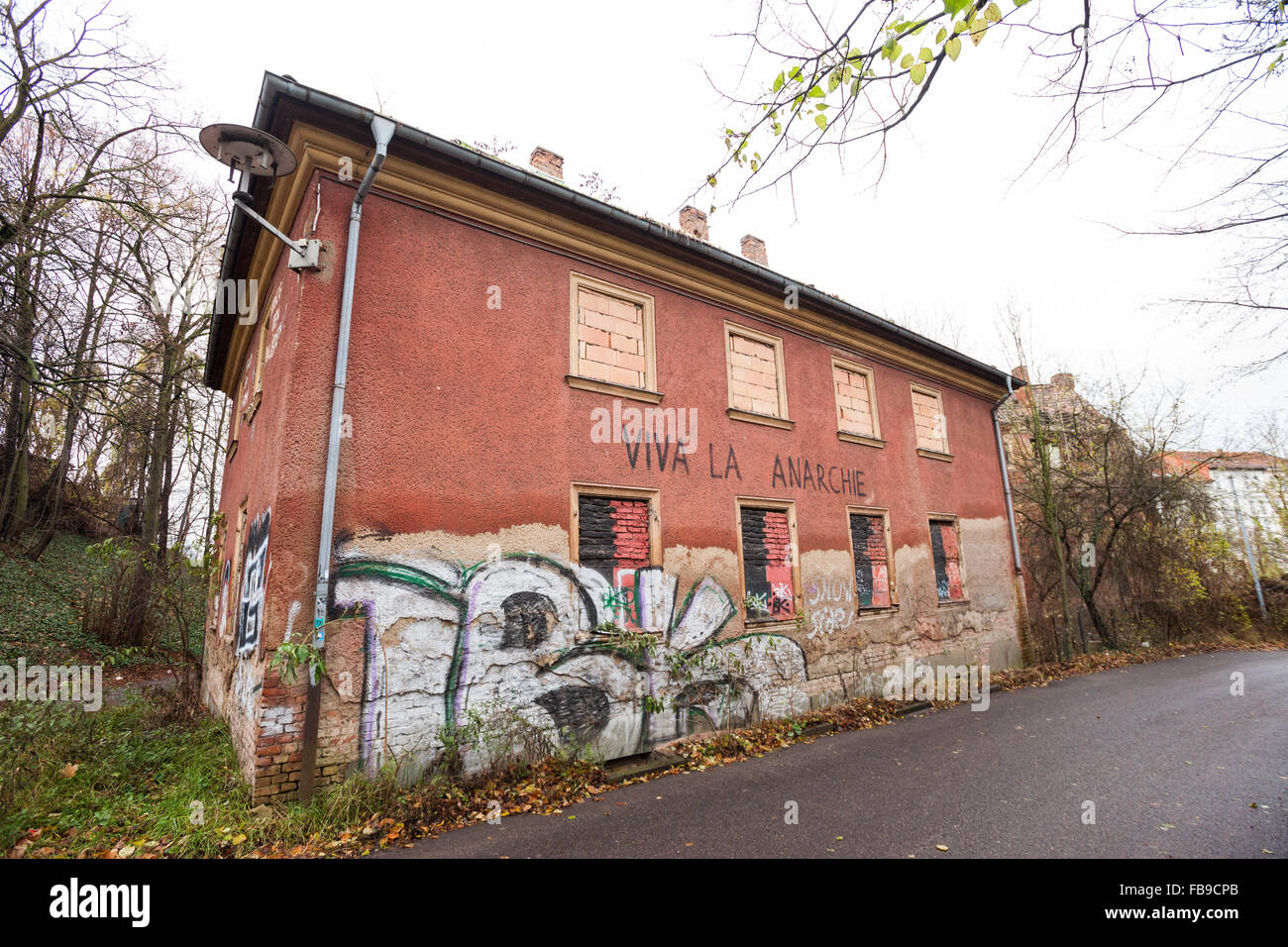 Ruins of an abandoned brick building with anarchist graffiti - Stock Image