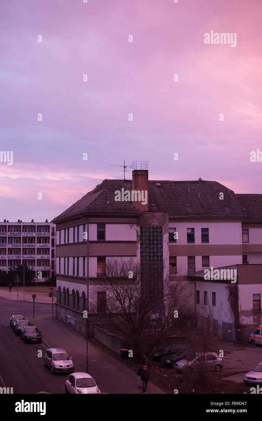 Run down building in the former East Germany, lit by dramatic pink sky Stock Photo