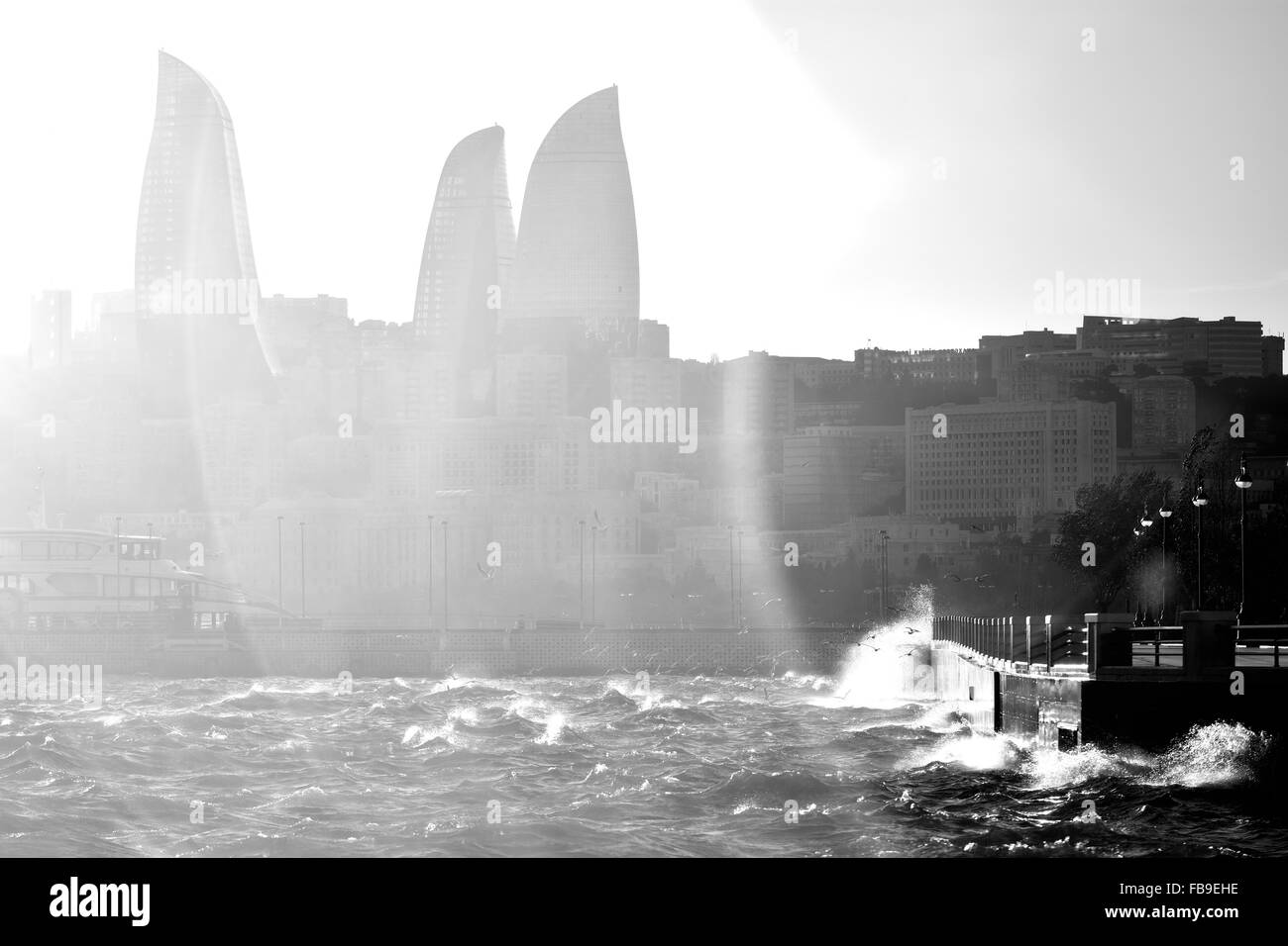 Stormy Caspian Sea with waves breaking against the Bulvar. Flare over Flame Towers in Baku, capital of Azerbaijan - Stock Image