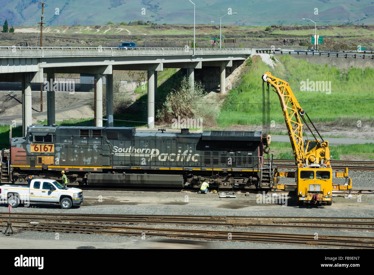 Workers using a mobile crane to repair a locomotive engine on the railroad. - Stock Image