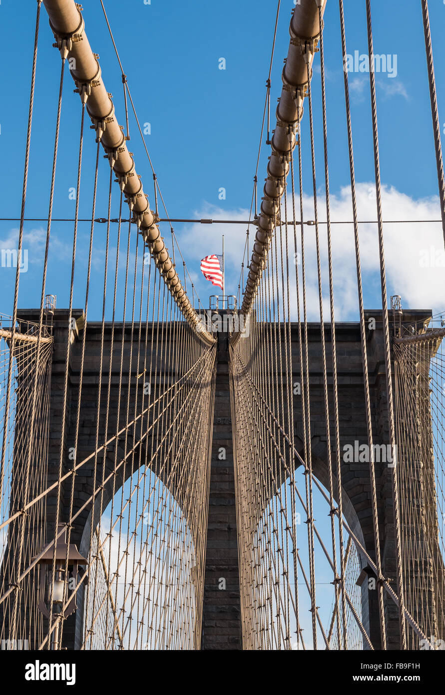 Looking upwards towards one of the towers of Brooklyn Bridge with granite and limestone brickwork and suspension - Stock Image