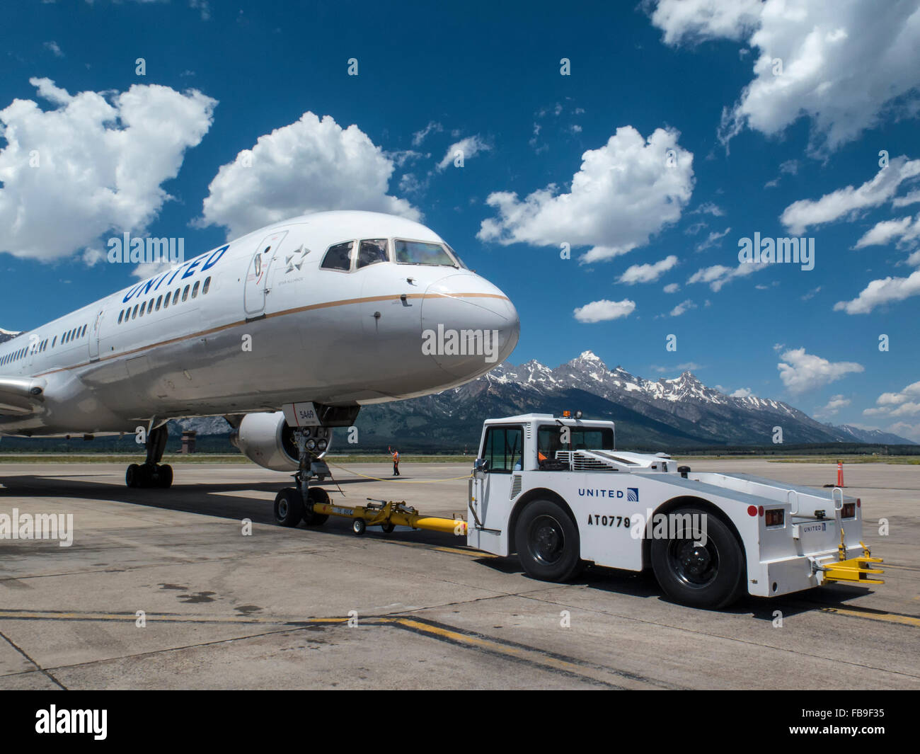 A United Airlines Boeing 757 in Jackson Hole Airport, Wyoming being pushed to the taxiway - Stock Image